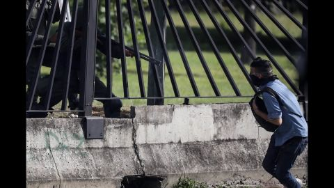 Protester David Jose Vallenilla is shot through a fence by a member of the National Guard near a military base in Caracas on Thursday, June 22. Vallenilla later died in the hospital after suffering three gunshot wounds to the chest.