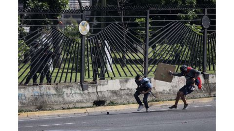 A protester carrying a Venezuelan flag moves in to provide cover after Vallenilla was shot.