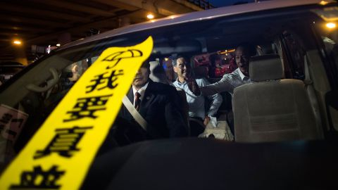 """A banner with the Chinese characters """"I want true universal suffrage"""" placed on the windscreen of a car carrying Hong Kong leader CY Leung."""