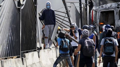 """Protesters tear down a fence at the La Carlota airbase outside Caracas on Friday, June 23. A soldier <a href=""""http://www.cnn.com/2017/06/23/americas/venezuela-protest-shooting-video/index.html"""">shot a demonstrator through the fence </a>at the base on the previous day, killing him."""