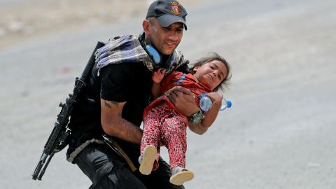 An Iraqi soldier helps transport a girl as residents flee their homes west of Mosul on Friday, May 26.