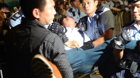 Activist Joshua Wong is arrested Wednesday in Hong Kong's Golden Bauhinia Square.