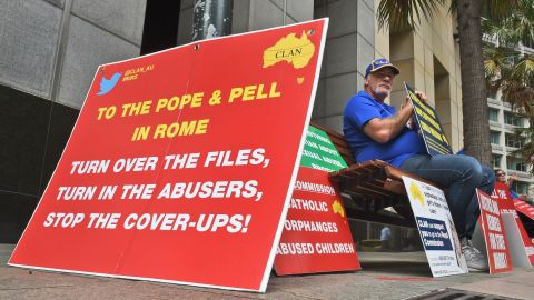 A protester holds a placard outside Australia's Royal Commission into child sex abuse in Sydney in March 2016.
