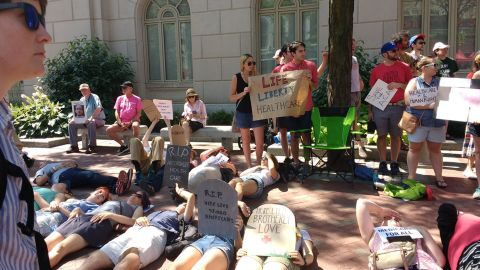 """Health care protesters hold """"die in"""" protest outside Sen. Pat Toomey's office in Philadelphia, Pennsylvania."""
