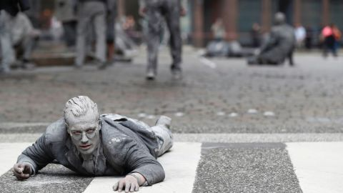 """A performer smeared with clay demonstrates during the art action """"1000 Gestalten"""" on July 5, 2017, on a street in Hamburg, northern Germany, where leaders of the world's top economies will gather for a G20 summit.  More than 100,000 anti-capitalist demonstrators, including several thousand leftwing extremists, are expected to descend on the Hanseatic city ahead of the two-day summit which opens on Friday, July 7, 2017. / AFP PHOTO / Odd ANDERSEN        (Photo credit should read ODD ANDERSEN/AFP/Getty Images)"""