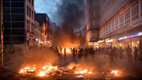 HAMBURG, GERMANY - JULY 07:  Demonstrators react next to a burning crush barrier during a demonstration against the G20 Summit on July 7, 2017 in Hamburg, Germany. Leaders of the G20 group of nations are arriving in Hamburg today for the July 7-8 economic summit and authorities are bracing for large-scale and disruptive protest efforts. (Photo by Thomas Lohnes/Getty Images)