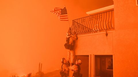 """Firefighters remove a US flag as flames from the """"Wall Fire"""" close in on a luxury home in Oroville, California on July 8, 2017. The first major wildfires after the end of California's five-year drought raged across the state on July 8, as it was gripped by a record-breaking heatwave."""