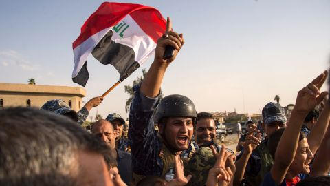 """Members of the Iraqi federal police wave the country's flag as they celebrate in the Old City of Mosul on July 9, 2017. <a href=""""http://www.cnn.com/2017/07/09/middleeast/iraq-mosul-victory-claimed/index.html"""" target=""""_blank"""">Iraq declared victory against ISIS forces in Mosul </a>after a grueling monthslong campaign. The battle to reclaim Mosul, the last major ISIS stronghold in Iraq, has been underway since fall 2016."""