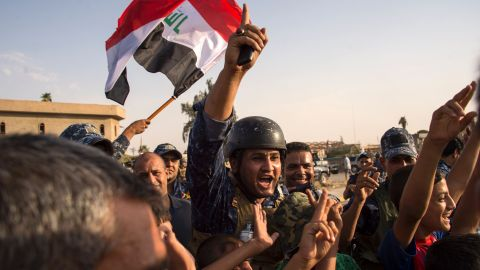 """Iraq's federal police members wave Iraq's national flag as they celebrate in the Old City of Mosul on July 9, 2017 after the government's announcement of the """"liberation"""" of the embattled city. Iraq declared victory against the Islamic State group in Mosul on July 9 after a gruelling months-long campaign, dealing the biggest defeat yet to the jihadist group."""