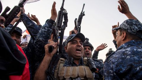 """Members of the Iraqi federal police forces celebrate in the Old City of Mosul on July 10, 2017 after the government's announcement of the """"liberation"""" of the embattled city from Islamic State (IS) group fighters. Iraqi Prime Minister Haider al-Abadi's office said he was in """"liberated"""" Mosul to congratulate """"the heroic fighters and the Iraqi people on the achievement of the major victory""""."""