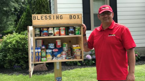 """Roman Espinoza stands beside his """"Blessing Box,"""" which allows residents of Watertown, New York, to donate and take food as needed."""