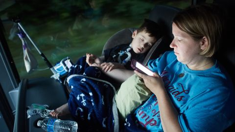 Gabe Michot, 4, holds his mother's arm as he sleeps on a bus ride from Baton Rogue to Washington DC on Sunday, July 9, 2017 in Raleigh, NC. Jessica Michot says Gabe was born premature and has several health issues including using a tracheostomy tube to breathe.   Photo by John Nowak/CNN