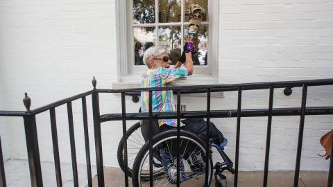 Becky Ogle knocks on a window of the Republican National Commitee headquarters with her prosthetic leg as she protests proposed cuts to Medicaid.