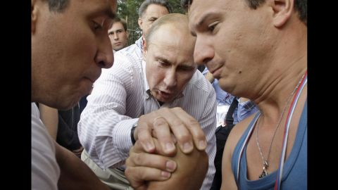 Putin officiates an arm-wrestling contest as he visits a youth educational forum near Russia's Lake Seliger in August 2011.