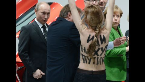 """A topless protester shouts at Putin and German Chancellor Angela Merkel during a visit to central Germany in April 2013. That month, Putin <a href=""""http://www.cnn.com/2013/04/25/world/europe/russia-putin-questions/index.html"""" target=""""_blank"""">defended his government's record on free speech</a> and rejected a claim that it uses """"Stalinist"""" methods to clamp down on critics and activists. Two international rights groups had issued scathing reports on Putin's presidency, saying changes to the law had helped authorities stifle dissent."""