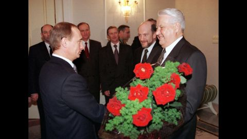Putin rose quickly through the political ranks. Here, he gives flowers to Russian President Boris Yeltsin during a farewell ceremony in Moscow in December 1999. Yeltsin, Russia's first democratically elected president, was resigning from office. Putin, his prime minister, was appointed acting president until the election, which Putin won several months later.