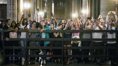 Tourists take pictures of Melania Trump as she visits the Notre Dame Cathedral on July 13.