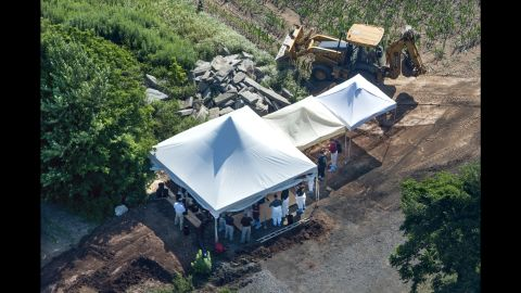 Investigators searched under tents on a property in Bucks County on July 12.