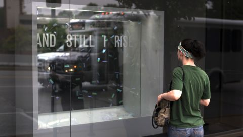 """A woman watches the """"And Still I Rise"""" exhibit from outside the Bruno David Gallery in St. Louis."""
