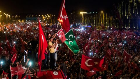 People watch on and wave flags as they listen to Turkey's President Recep Tayyip Erdogan during his speech.