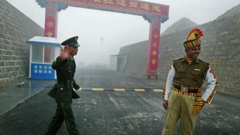 A Chinese soldier (L) and an Indian soldier stand guard at the Chinese side of the ancient Nathu La border crossing between India and China.