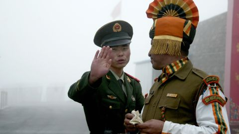 A Chinese soldier stands near an Indian soldier at the ancient Nathu La border crossing.