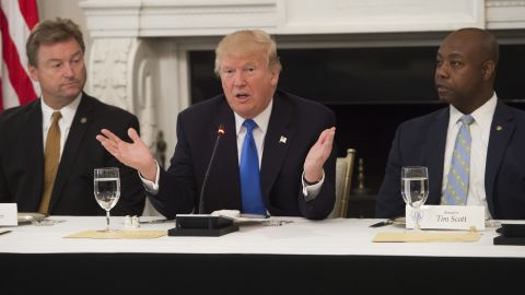 US President Donald Trump speaks alongside US Senator Dean Heller (L), Republican of Nevada, and US Senator Tim Scott (R), Republican of South Carolina, during a meeting with Republican Senators to discuss the health care bill in the State Dining Room of the White House in Washington, DC, July 19, 2017. (SAUL LOEB/AFP/Getty Images)