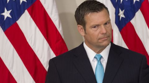 Kansas Secretary of State Kris Kobach listens as President Donald Trump speaks during the first meeting of the Presidential Advisory Commission on Election Integrity in the Eisenhower Executive Office Building next to the White House in Washington, DC, July 19, 2017.