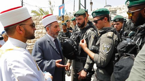 Palestinian clerics speak with Israeli border guards outside the Lions' Gate in Jerusalem's Old City on July 21.