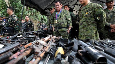 Philippines President Rodrigo Duterte examines militant weapons that were seized at Camp Ranao in Marawi.