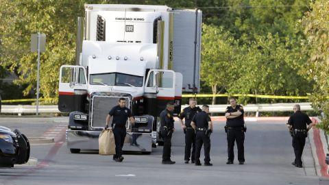 San Antonio officers investigate the scene where people were found dead in a tractor-trailer outside a Walmart.