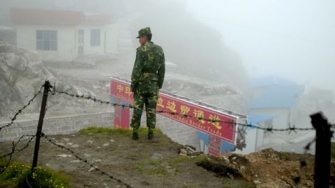 A Chinese soldier stands guard at the ancient Nathu La border crossing between India and China