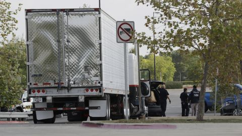 San Antonio police officers investigate the tractor-trailer that carried undocumented immigrants.