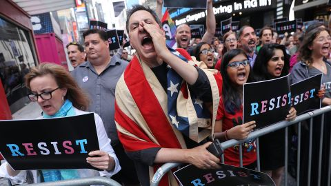 """Dozens of protesters gather in Times Square near a military recruitment center to show their anger at President Donald Trump's decision to reinstate a ban on transgender individuals from serving in the military on July 26, 2017 in New York City. Trump citied the """"tremendous medical costs and disruption"""" for his decision."""