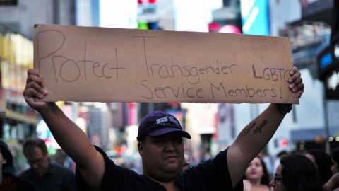 """A protester displays a placard during a demonstration against US President Donald Trump, in front of the US Army career center in Times Square, New York, on July 26, 2017.  Trump announced on July 26 that transgender people may not serve """"in any capacity"""" in the US military, citing the """"tremendous medical costs and disruption"""" their presence would cause. / AFP PHOTO / Jewel SAMAD        (Photo credit should read JEWEL SAMAD/AFP/Getty Images)"""