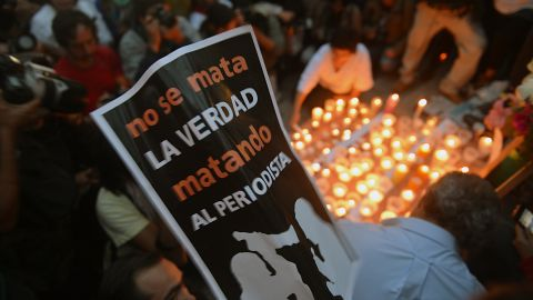 """Colleagues, relatives and friends of murdered journalists place candles and pictures in an altar erected at the Independence Angel monument in Mexico City on May 5, 2012 during a vigil to protest against violence towards the press. On Thursday Mexican security forces found the dismembered bodies of missing news photographers Guillermo Luna Varela and Gabriel Huge and two other people in bags dumped in a canal in the eastern state of Veracruz. The bodies of the photographers, who worked for the Veracruz news photo agency, also showed signs of torture. The postre reads """"The Truth is Not Killed by Killing The Journalist"""".   AFP PHOTO/Yuri CORTEZ        (Photo credit should read YURI CORTEZ/AFP/GettyImages)"""