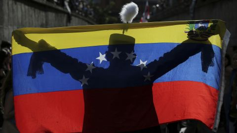 A demonstrator dressed as Venezuelan independence hero Simon Bolivar is silhouetted against a national flag in Caracas on Monday, July 24.