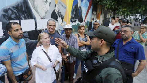 Voters receive instructions by a Venezuelan Bolivarian National Guard officer outside a polling station during the election for a constitutional assembly in Caracas, Venezuela, Sunday, July 30, 2017.