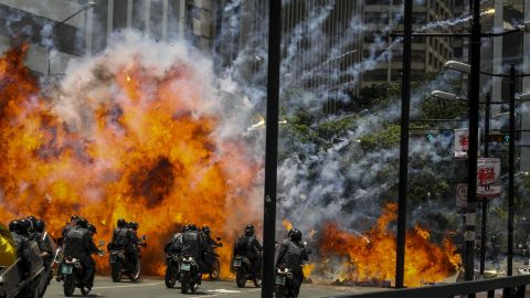 """Members of Venezuela's national police are caught in an explosion as they ride motorcycles near Altamira Square in Caracas on July 30. Venezuela <a href=""""http://www.cnn.com/2017/05/09/americas/venezuela-violin-protester/"""" target=""""_blank"""">has seen widespread unrest</a> since March 29, when the Supreme Court dissolved Parliament and transferred all legislative powers to itself. The decision was later reversed, but protests have continued across the country, which is also in the midst of an economic crisis."""