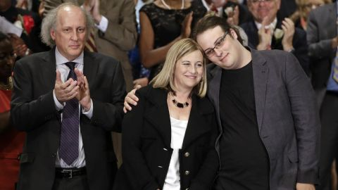 Nashville Mayor Megan Barry is hugged by her son, Max, as her husband, Bruce, applauds after she was sworn into office in Nashville.