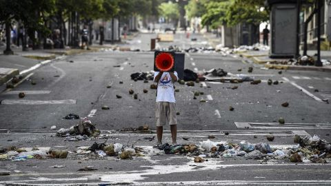 A demonstrator shouts slogans through a traffic cone during an anti-government protest in Caracas on July 30.
