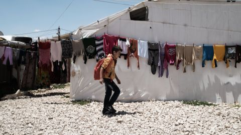 Syrian refugee Yamen, 10, passes laundry at an informal settlement in the Bekaa Valley, Lebanon.