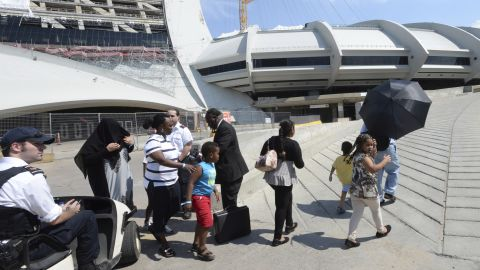 Asylum seekers take a walk outside Olympic Stadium as security guards look on in Montreal, Wednesday, Aug. 2, 2017. The stadium will be housing asylum seekers after a spike in the number of people crossing at the United States border in recent months. (Ryan Remiorz/The Canadian Press via AP)