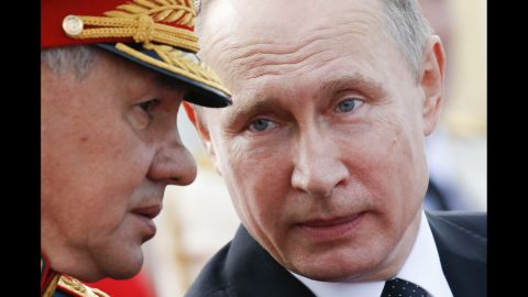 Russian President Vladimir Putin (R) speaks with Defence Minister Sergei Shoigu as they attend a ceremony for Russia's Navy Day in Saint Petersburg on July 30, 2017.