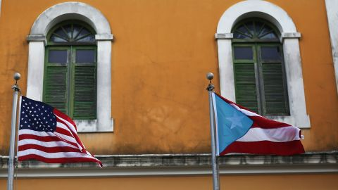 SAN JUAN, PUERTO RICO - JUNE 30:  An American flag and Puerto Rican flag fly next to each other in Old San Juan a day after the Puerto Rican Governor Alejandro Garcia Padilla gave a televised speech regarding the governments $72 billion debt on June 30, 2015 in San Juan, Puerto Rico.  The Governor said in his speech that the people will have to sacrifice and share in the responsibilities for pulling the island out of debt.  (Photo by Joe Raedle/Getty Images)