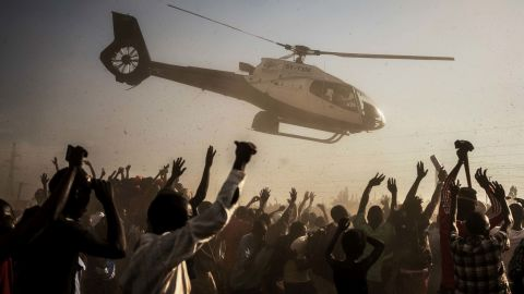 Supporters of Kenyan presidential candidate Raila Odinga wave as he departs in a helicopter after addressing a rally in Kisumu on August 3.