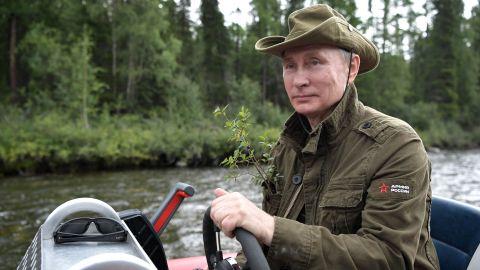 Putin guides a boat this week during his Siberian vacation.