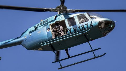 Members of the Venezuelan armed forces fly over Valencia in a helicopter while citizens demonstrate in support of a group that staged a paramilitary uprising at the Paramacay military base on August 6.