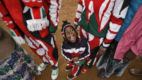 Joseph Njoroge Kimani, 3, stands with his parents as they wait to vote in Gatundu.