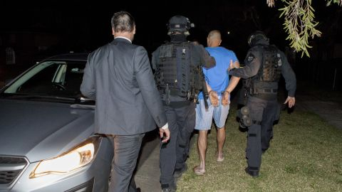 A suspect in an international drug bust involving the law enforcement agencies of three countries and two tons of drugs seized is escorted in handcuffs by Australian police.